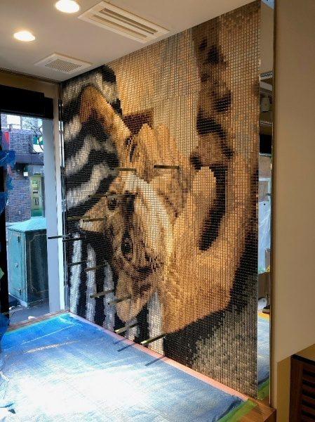 人に撫でられている猫絵柄のアートモザイクタイル施工壁面