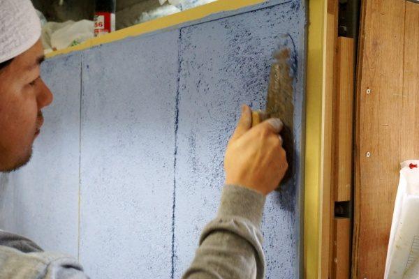 青いガラス洗い出しの試験施工中の様子。塗り付け工程
