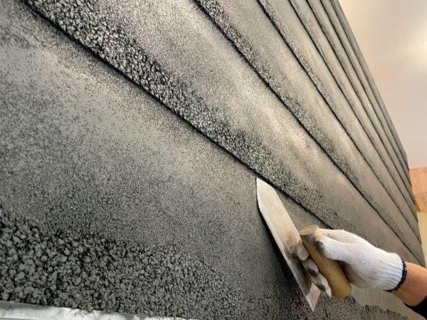 黒色の塗り版築瓦葺き風仕上げ壁。鏝で施工中の様子