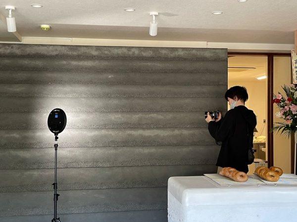 黒色の塗り版築瓦葺き風仕上げ壁。カメラマンさんの撮影の様子
