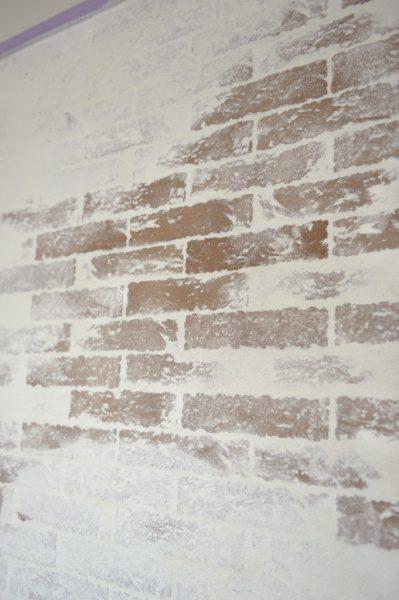 ブリックタイルを張り白い左官材を塗った壁